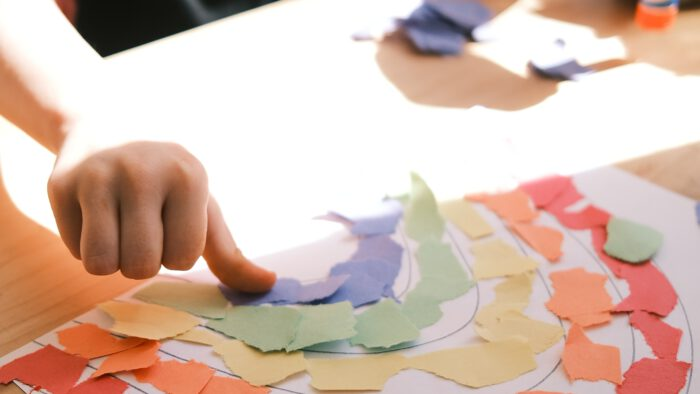 Child working on a rainbow picture
